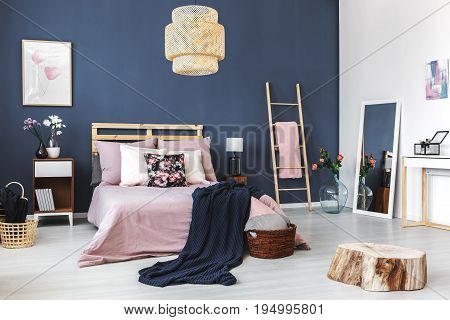 Stylish cozy hotel room with king-size bed and decorative wooden stump