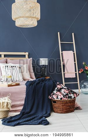 Decorative floral cushion in brown basket next to bed with blue blanket
