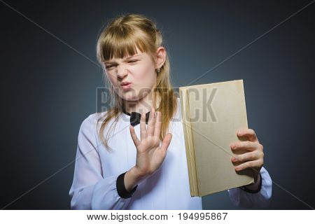 angry or stressed girl with book. Closeup Portrait of handsome teen on grey background. studies concept.