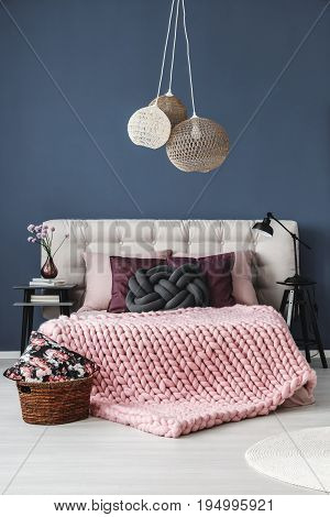 Designer knotted pillow on the bed with pastel pink bedding