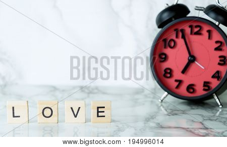Love text on marble with red alarm clock