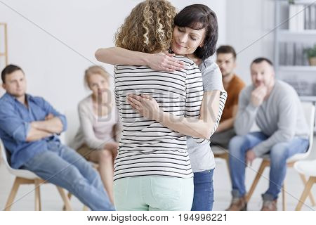 Concerned woman comforting another woman in support group poster