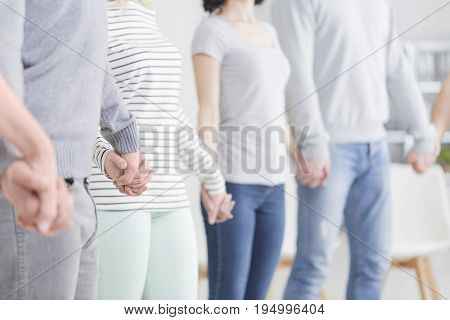 People holding hands during support group meeting