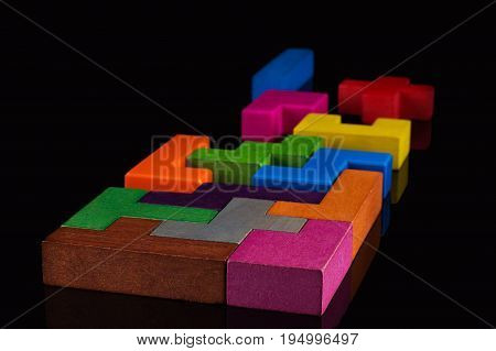 Abstract Background. Different colorful shapes wooden blocks on black background. Geometric shapes in different colors. Concept of creative logical thinking or problem solving. Copy space.