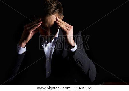 Tomar Retratos de empresario moderno graves en traje oscuro, sentado en el escritorio de oficina, mirando hacia abajo