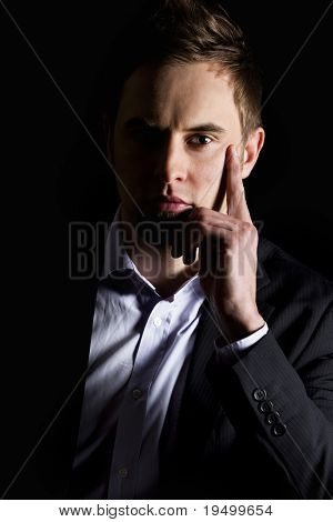 Low-key close up portrait of young serious businessman in dark suit sitting at desk looking straight, isolated on black background