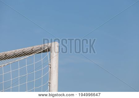 The top corner of a soccer (football) goal with blue sky background
