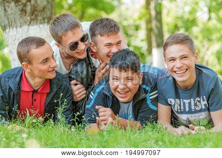 A group of young men laughs cheerfully. Young people Vadym, Denys, Bogdan, Nazar, Anatoly are pleased with the end of the school year. The photo was taken on May 23, 2017 in Yahotyn, Ukraine.