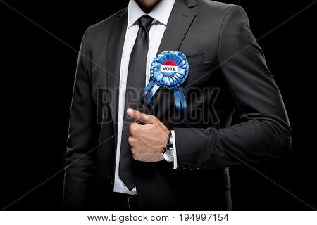 Cropped View Of Businessman In Black Suit With Vote Badge, Isolated On Black