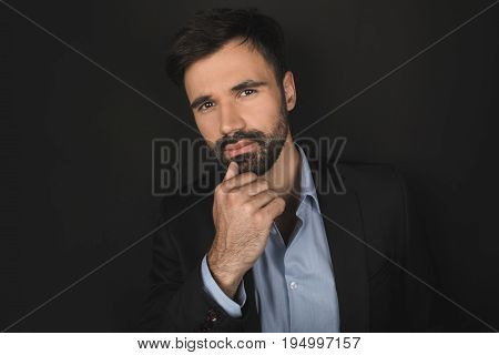 Handsome Bearded Pensive Businessman Posing In Black Suit, Isolated On Black