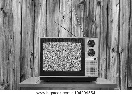 Vintage television with rustic wood wall and static screen in black and white.