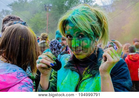 Moscow, Russia - June 3, 2017: Portrait of a nice blonde woman, strewn with green paint after Holi-expression at a joy summer festival of colour. Indian festival Holi turned into a fun event