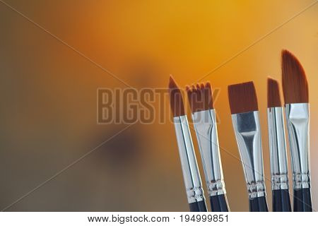 Artistic brushes in the workshop. Brushes artist on blur yellow-orange background in the studio for artists.