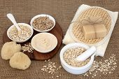 Natural oat skincare treatment and cleansing products on hessian background. poster