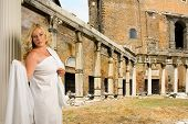 woman in toga with a view of trajans market and the roman forum poster