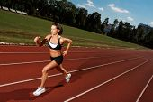 Athletic woman running on track poster