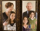 grandparents and grandchildren with Hanukkia, at the window poster