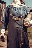 Scandinavian middle class woman in historical suit posing over village. Her apparel based on archaeological sites on Island of Gotland. Late 10th - 11th centuries. poster