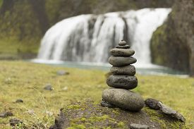 Stack of rocks next to a peaceful waterfall
