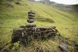 Stack of rocks next to a peaceful grass field
