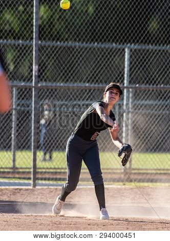 Female Teenage Softball Player In Black Uniform Throwing Ball Across Infield For The Out In A Cloud