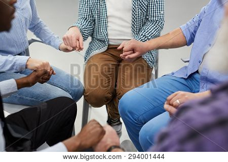 High Angle Close Up Of People Holding Hands Sitting In Circle During Therapy Session In Support Grou