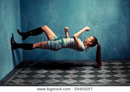 woman in boots and jeans shorts climb up  the wall in grungy room