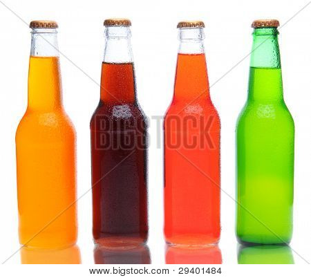 Four assorted soda bottles on white with reflection.