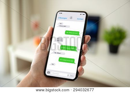 Female Hands Holding Phone With App Messenger On The Screen In The House In Room