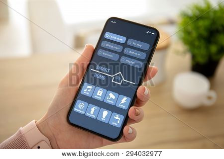 Female Hands Holding Phone With App Smart Home On The Screen In The House In Room