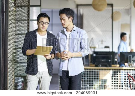 Two Young Asian Coworkers Discussing Business While Walking In Office.
