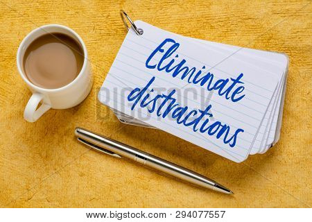 Eliminate distractions - handwriting on a stack of index cards with a cup of coffee and  a pen against yellow textured paper