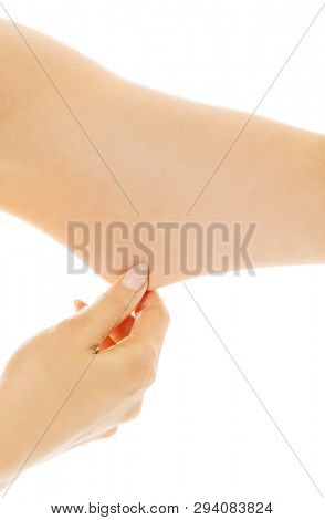 Close up view of woman stretching the skin under her arm on white background.