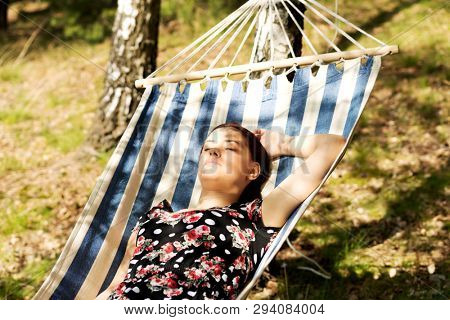 Young woman lying in a hammock under trees in sunny summer day.
