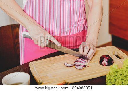 Female hands cutting bulb Edelweiss onionon wooden board, in kitchen.
