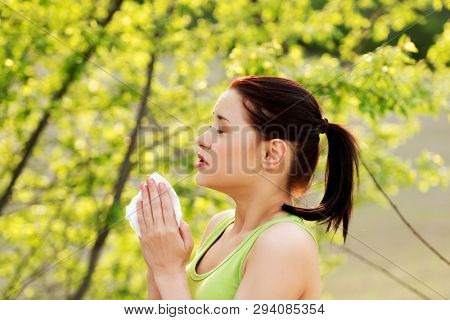 Young woman is sneezing with tissue outside. Pollen allergy concept.