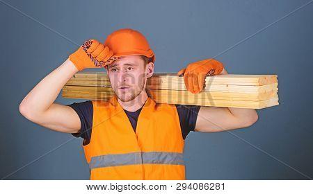 Carpenter, Woodworker, Strong Builder On Serious Face Carries Wooden Beam On Shoulder. Man In Helmet