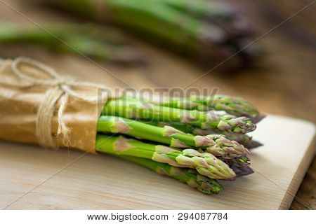 Bunch Of Raw Asparagus On Wooden Table. Green Fresh Harvested Vegetable. Healthy Meal. Vegetarian An