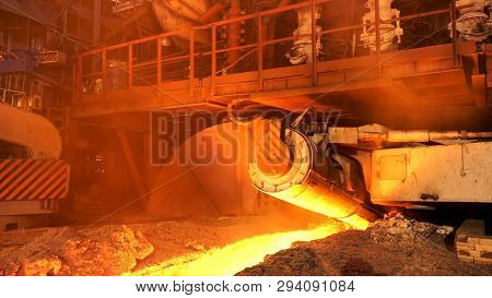 Side view of melting steel furnace big moving element in the hot foundry, metallurgy concept. Stock footage. Hot steel flowing in the chute at the metal melting factory. poster