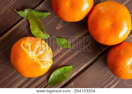 Group Of Four Whole Fresh Orange Mandarine With Green Leaves One Fruit Is Half Peeled Flatlay On Bro