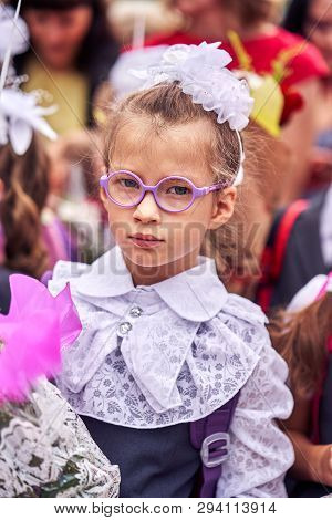 A Girl Child In School Festive Uniform With Bows, Glasses And A School Bag On Her Back Is Standing I