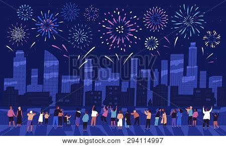 Crowd Of People Watching Fireworks Displaying In Dark Evening Sky And Celebrating Holiday Against Ci