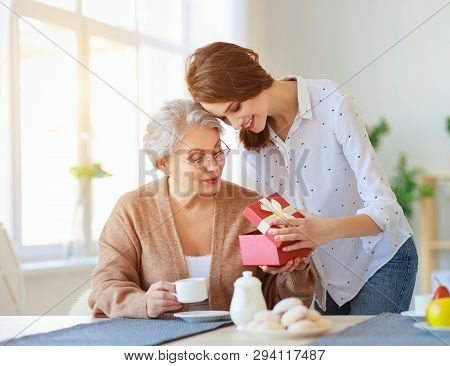 Happy Mother's Day! Adult Daughter Gives Gift  And Congratulates An Elderly Mother On Holiday .