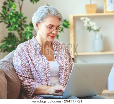 The Happy Old Woman Senior Working At Computer Laptop At Home
