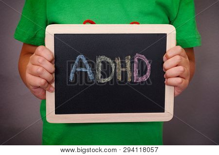 Young Boy Holds Adhd Text Written On Blackboard. Adhd Is Attention Deficit Hyperactivity Disorder. C