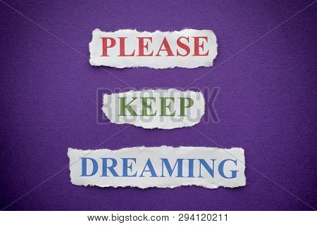Please Keep Dreaming Phrase On Purple Background With Vignette.