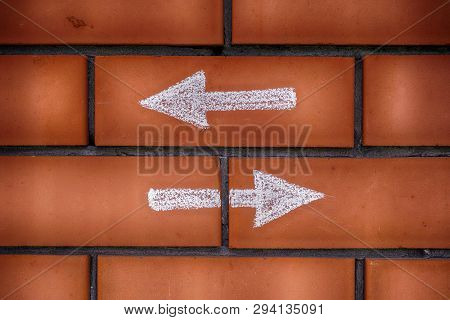 Two Arrows Pointing Forward And Backward Drawn On Bricks. Two Different Choices. Dilemma Concept.