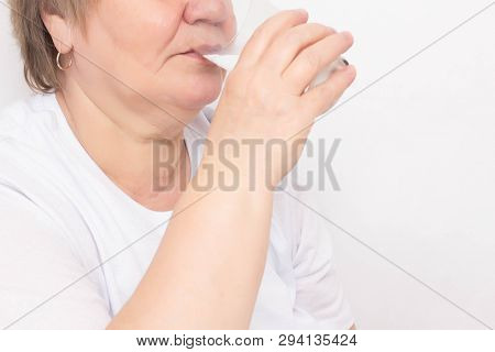 Elderly Woman Drinks Water From A Glass On A White Background, Concept Of Loss Of Body Fluid In The
