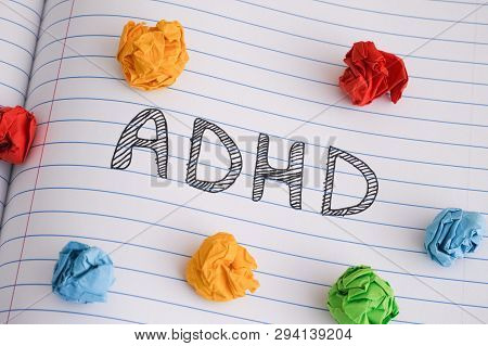 Adhd. Abbreviation Adhd On Notebook Sheet With Some Colorful Crumpled Paper Balls On It. Close Up. A