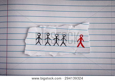 Piece Of Paper With Drawn People And The Red One Is The Odd One Out. Concept Image. Close Up.